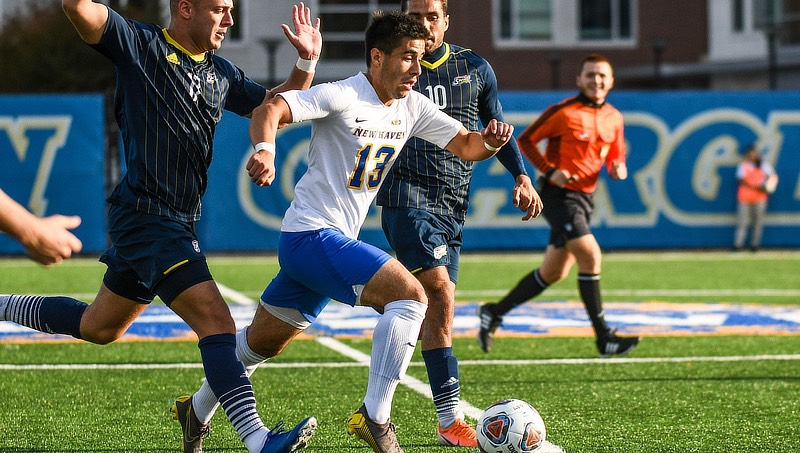 Image of JP Viruet '22 (No. 13) in a match against Southern New Hampshire University.