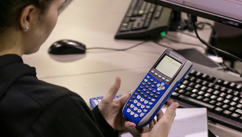 Image of a student using their calculator.